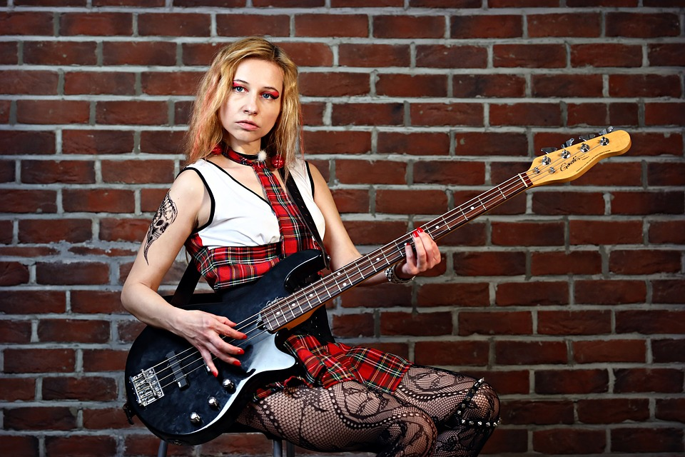 Girl posing for photo with a bass guitar