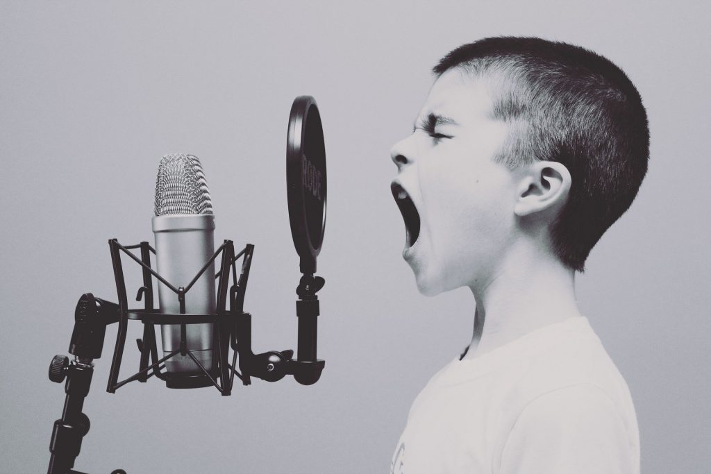Child singing into an old-style microphone